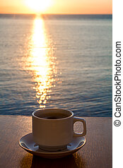 White Coffee cup in the morning time with sunrise path on the water.