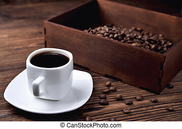 white coffee cup, morning side light coffee beans wooden coffee box, natural wooden background