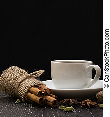 white coffee cup on a saucer, cinnamon, spices