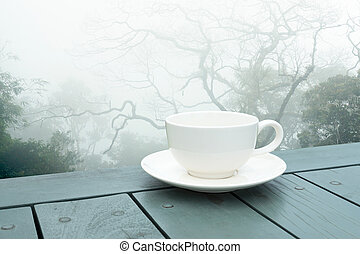 White coffee cup on green table in the morning with mist.