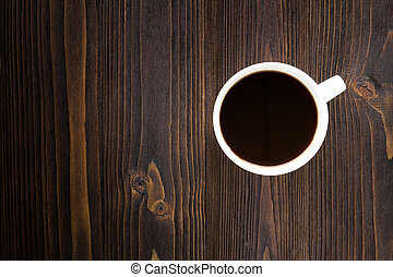 White coffee cup with black coffee on wooden table.