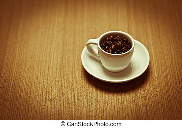 white coffee mug on white plate filled with beans - A white...