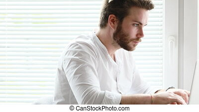 white collar bearded man typing then watching outside -...