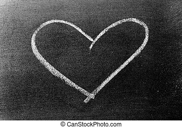 White color chalk hand drawing in heart shape on blackboard background