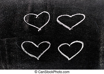 White color chalk hand drawing in set of heart shape on blackboard background