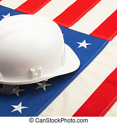 White color construction helmet laying over US flag - ...