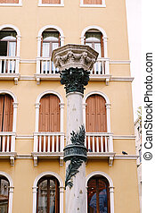 White column with ornament on the background of a yellow building in Venice, Italy