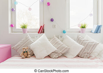 White comfortable sofa with pillows and teddy bear