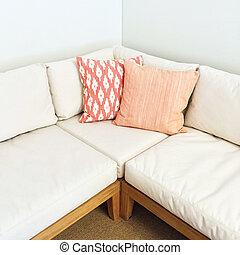 White corner sofa with pink cushions