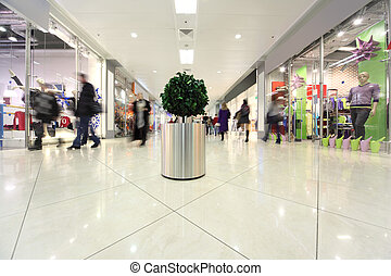 white corridor in shopping mall, potted tree and people in motion