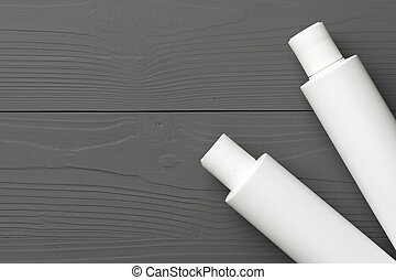 White cosmetic container on gray wooden background