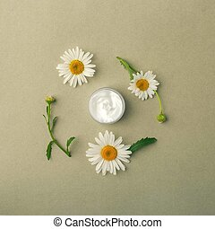 White cosmetics concept on the green pastel background with camomile flowers. Summer beauty flat lay. Top view, Copy space
