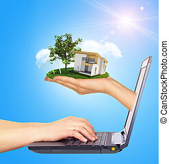 White cottage in hand with green roof of screen laptop. Background sun shines brightly on right