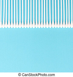 White cotton buds on a blue background lie in a straight line at the top of the photo