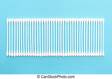 White cotton buds on blue background lie in line