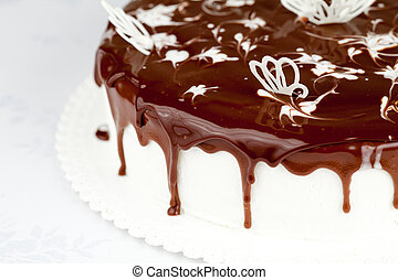 white cream cake covered by chocolate on table