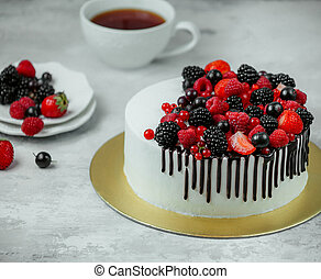 white cream cake with berries on the table