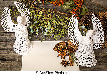 White crocheted angel with a Christmas envelope and cones on wooden background