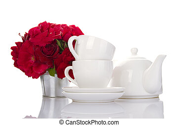 White crockery for tea and a bouquet of roses - White...