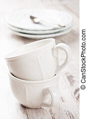 White crockery for tea, cups, milk jug and teapot on white...