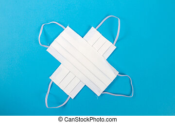 white cross with protection mask on blue background