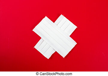 white cross with protection mask on red background