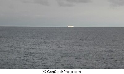 White cruise liner moving to the sea at cloudy day