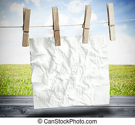 White crumpled paper hung on a laundry line over wooden...