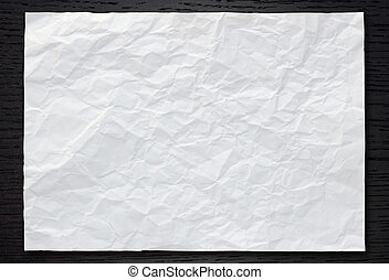 White crumpled paper on dark wood background