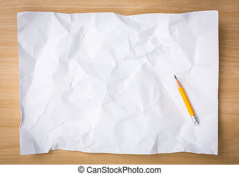White crumpled paper with pencil on a wooden desk