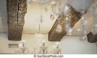White crystal chandeliers hang on ceiling in hall indoor....