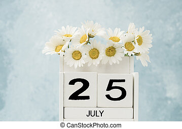 White cube calendar for july decorated with daisy flowers over blue with copy space
