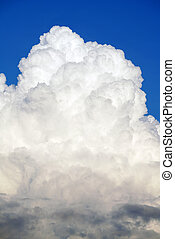 White cumulonimbus clouds in clear blue sky