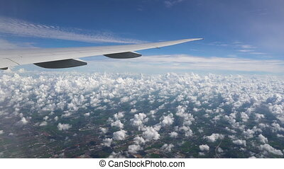 White cumulus clouds, green fields, roads and buildings under the wing of the aircraft