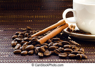 White cup and coffee beans on a dark wattled background