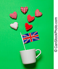 White cup and flag of United Kingdom with heart shapes