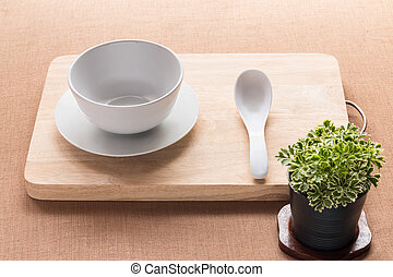 White cup and spoon on a wooden tray decorate with miniature tree for food table on brown tablecloth background.