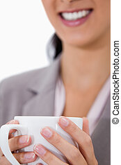 White cup being held by female hands