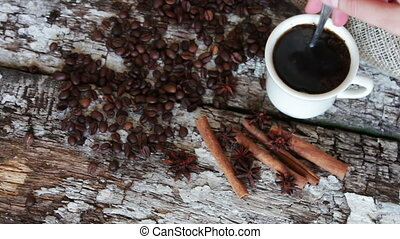 white cup full of fragrant hot coffee next to the cinnamon...