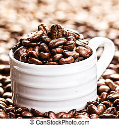 White Cup full of roasted coffee beans on heap of coffee ...
