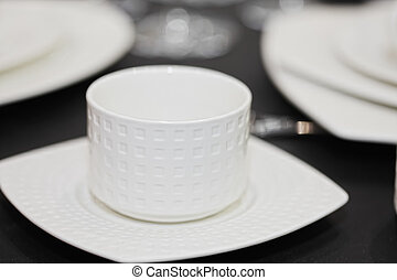 White cup in saucer closeup photo