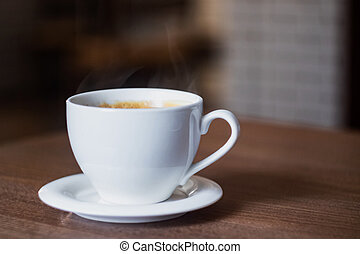 White cup of aromatic coffee on a wooden table