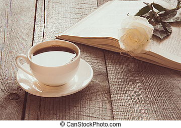 White cup of black coffee and open book with white rose on wooden board. Vintage. Close up.