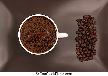 white cup of black coffee on a brown plate with coffee beans