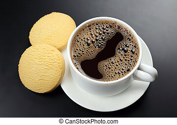 white cup of black coffee with biscuits on a dark background