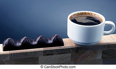 white Cup of black coffee with chocolate on a wooden frame