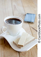 White cup of black coffee with chocolate wafers and mobile in th