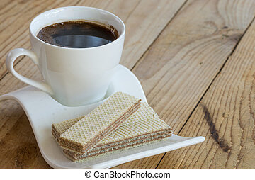White cup of black coffee with chocolate wafers