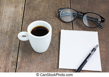 White cup of black coffee with note and pencil on wood table