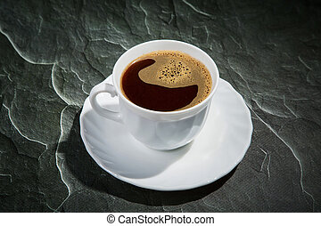 white cup of coffee and a saucer on a black background